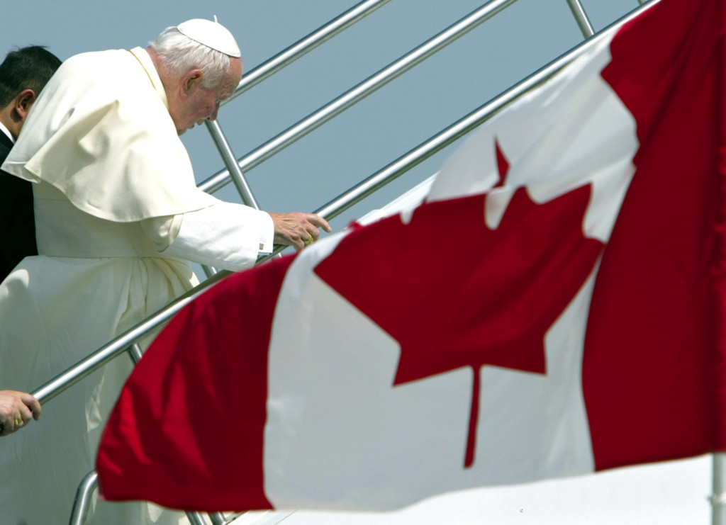 Pope John Paul II climbs the steps to an airplane as he leaves Toronto July 29 after the eighth international World Youth Day. Rejuvenated from his contact with youths from around the world, he left for Guatemala City to canonize Blessed Pedro de San Jose Betancur. (CNS photo from Reuters) (July 29, 2002) See WYD-DEPART July 29, 2002.